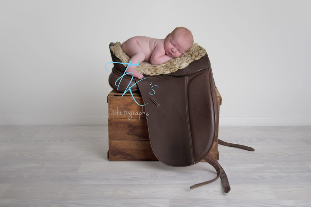 TK's Photography Launceston newborn baby girl curled up on horse saddle