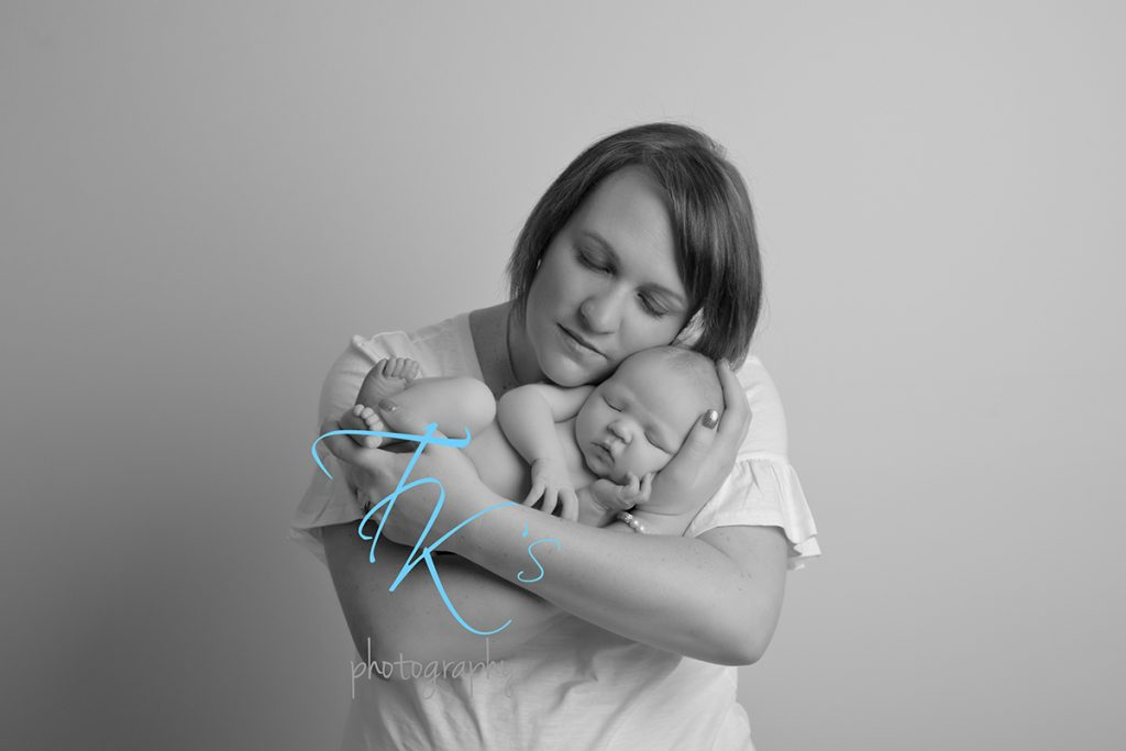 TK's Photography Launceston mum cuddling newborn baby girl in arms