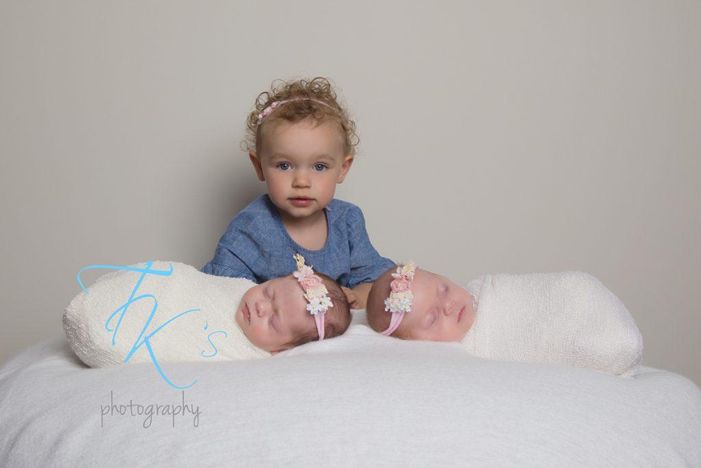 twin newborn baby girls with big sister