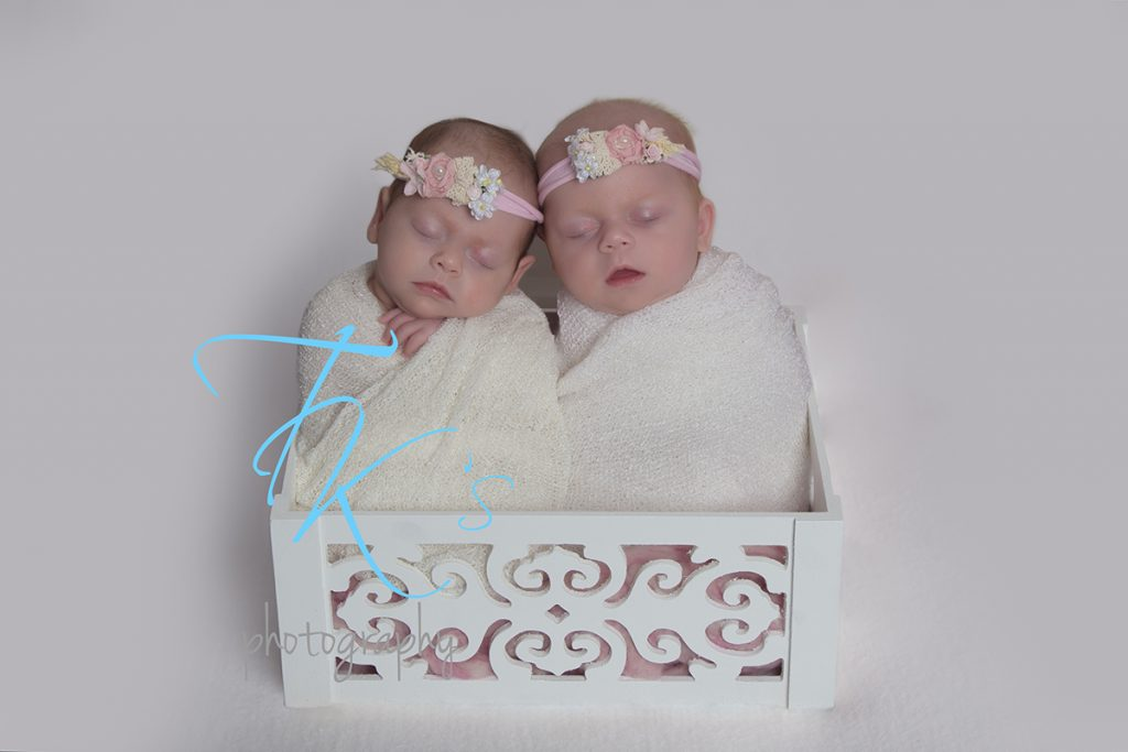 twin newborn baby sisters wrapped in box