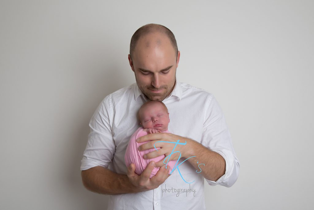 daddy holding newborn baby girl wrapped in pink