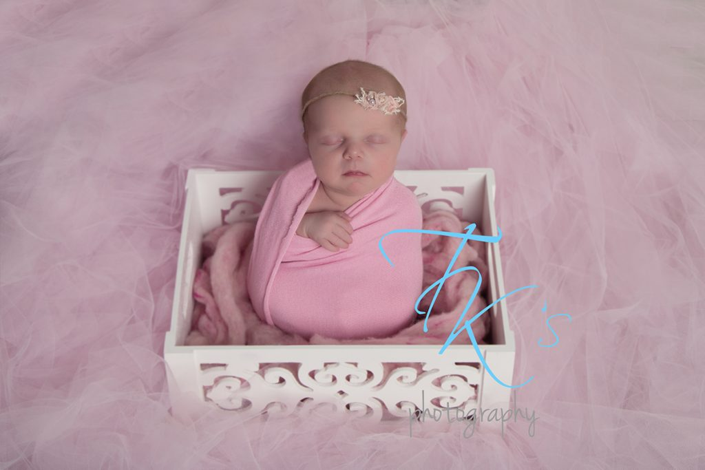 newborn baby girl wrapped in pink sitting in box surrounded by tulle