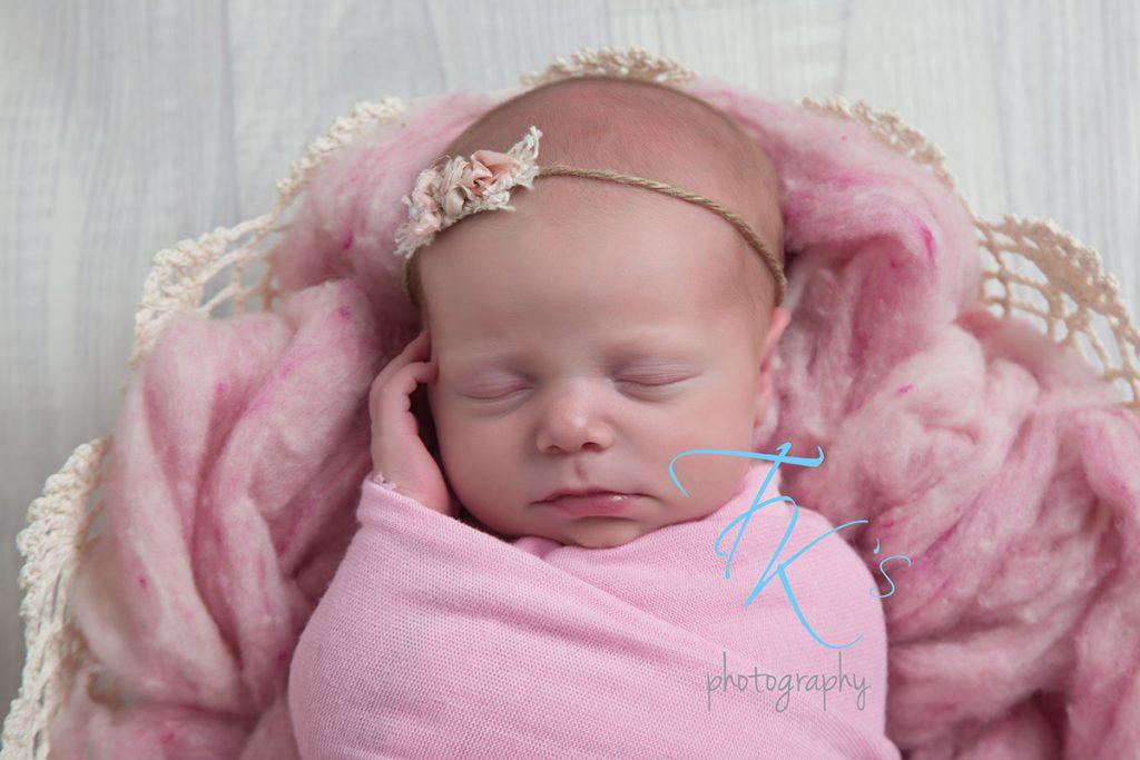 newborn baby girl close up face pink headband