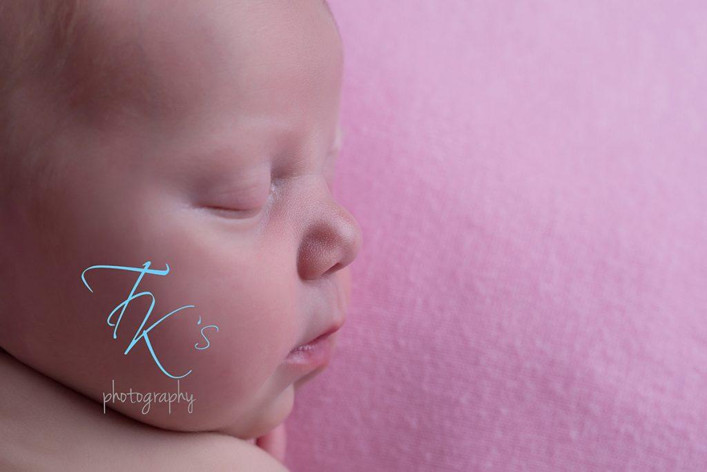 newborn baby girl close up profile milk spots on nose