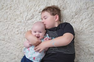 baby girl being kissed by big brother
