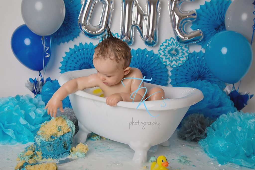 boy reaching over for more cake while in the bathtub