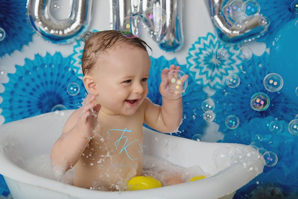 child in the bath tub splashing with rubber ducks
