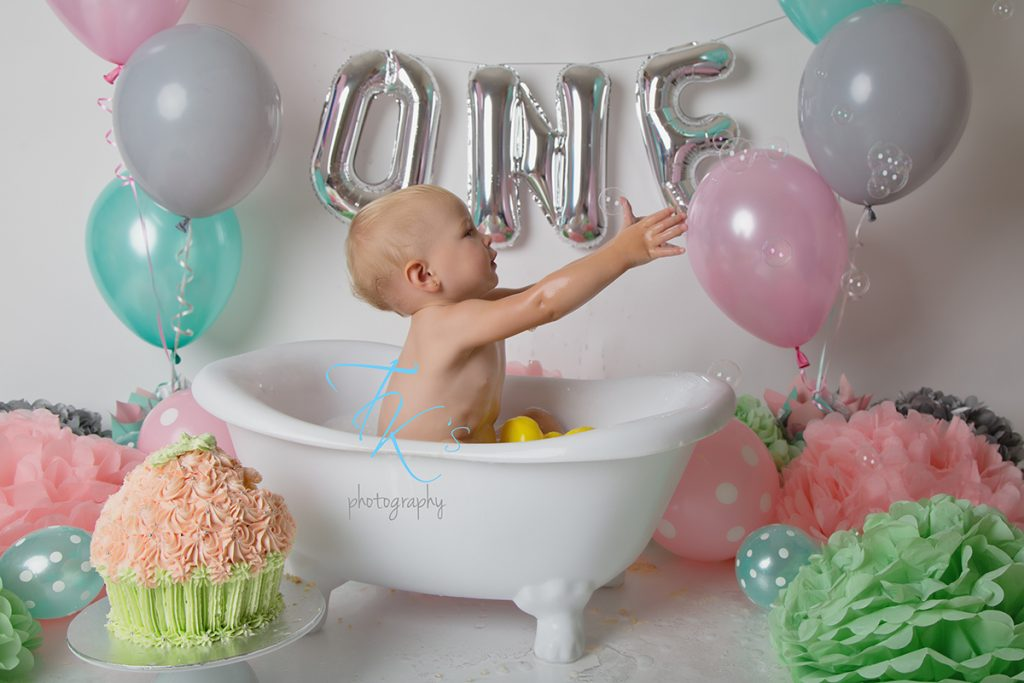 baby girl sitting in tub reaching for bubbles