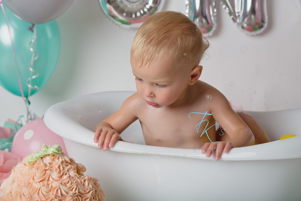 baby girl sitting in tub looking over at cake