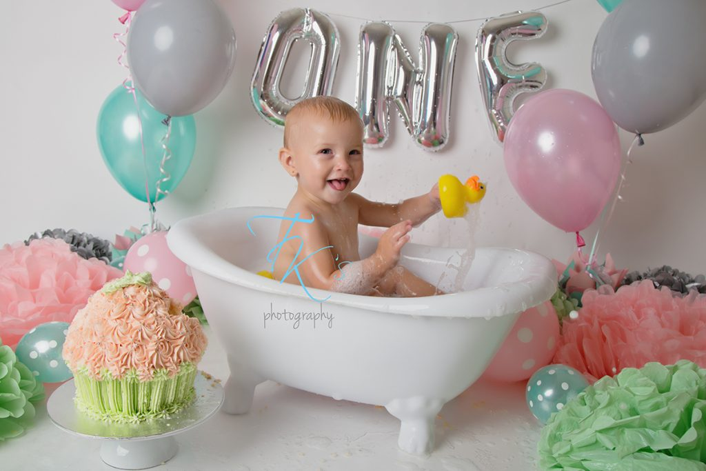 baby girl smiling in tub playing with rubber duck