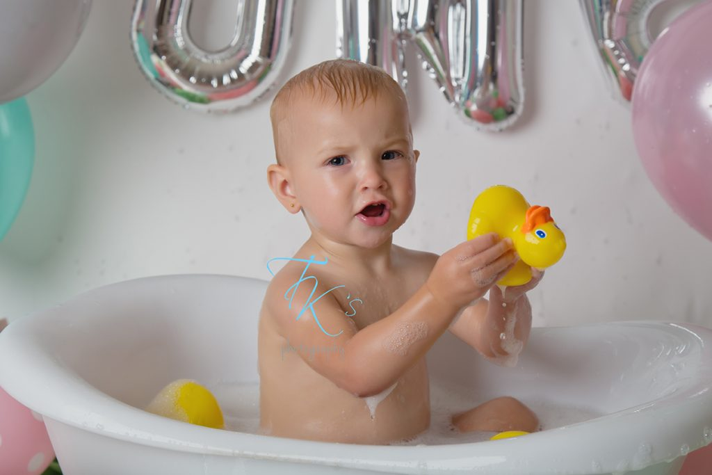 baby girl in tub squeezing rubber duck