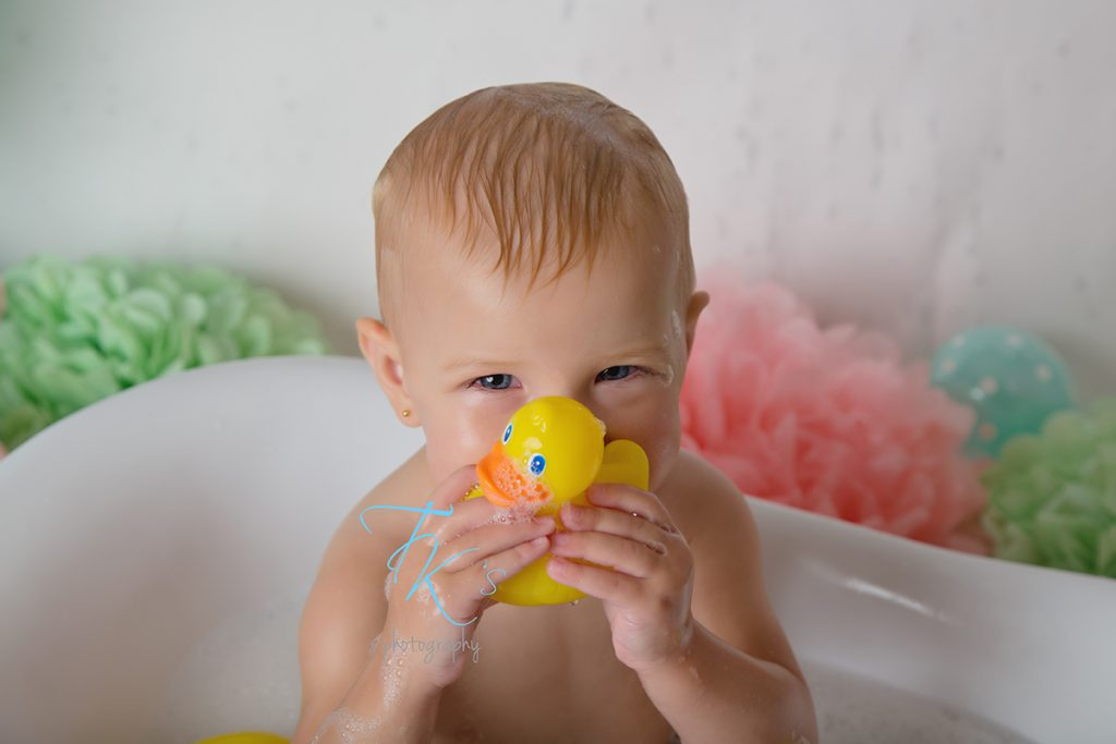 baby girl in tub chewing rubber duck
