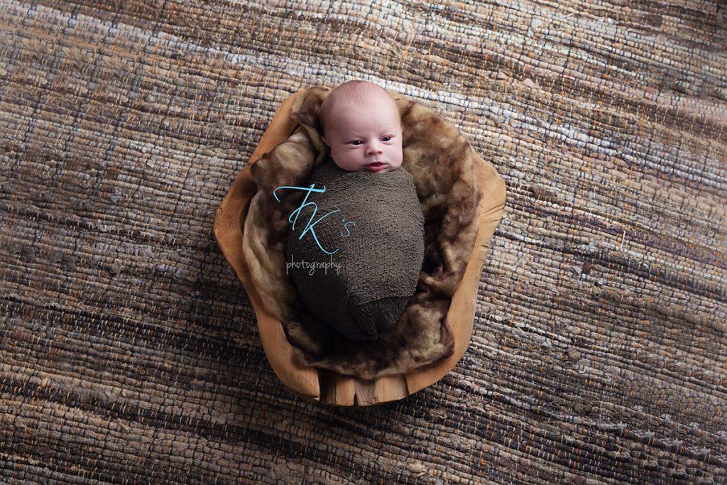 newborn baby boy in wooden bowl